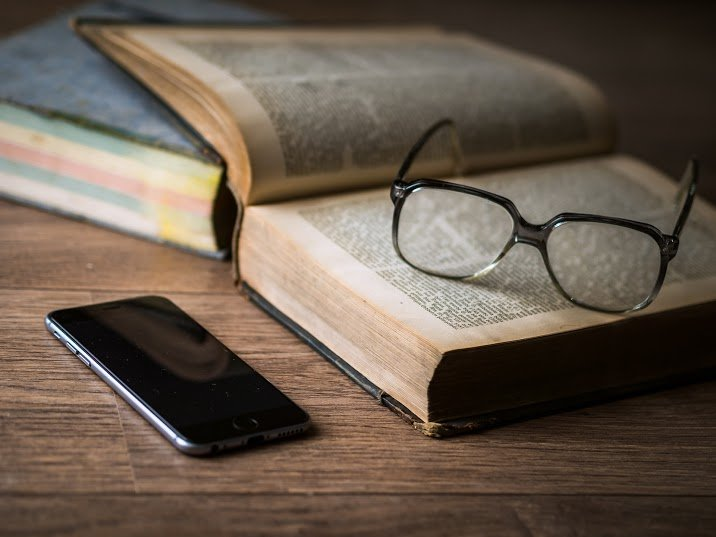 A phone and an open book with glasses on a table